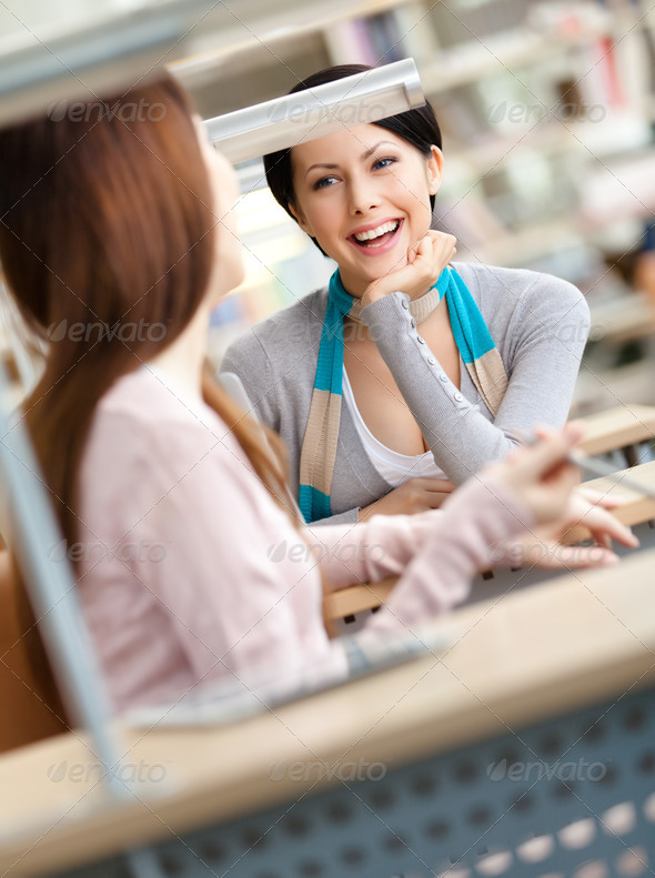 Two girlfriends communicate sitting at the desk - Stock Photo - Images