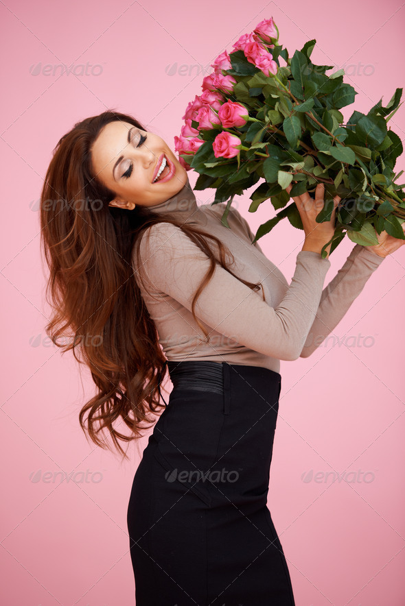 Happy vivacious woman with pink roses - Stock Photo - Images