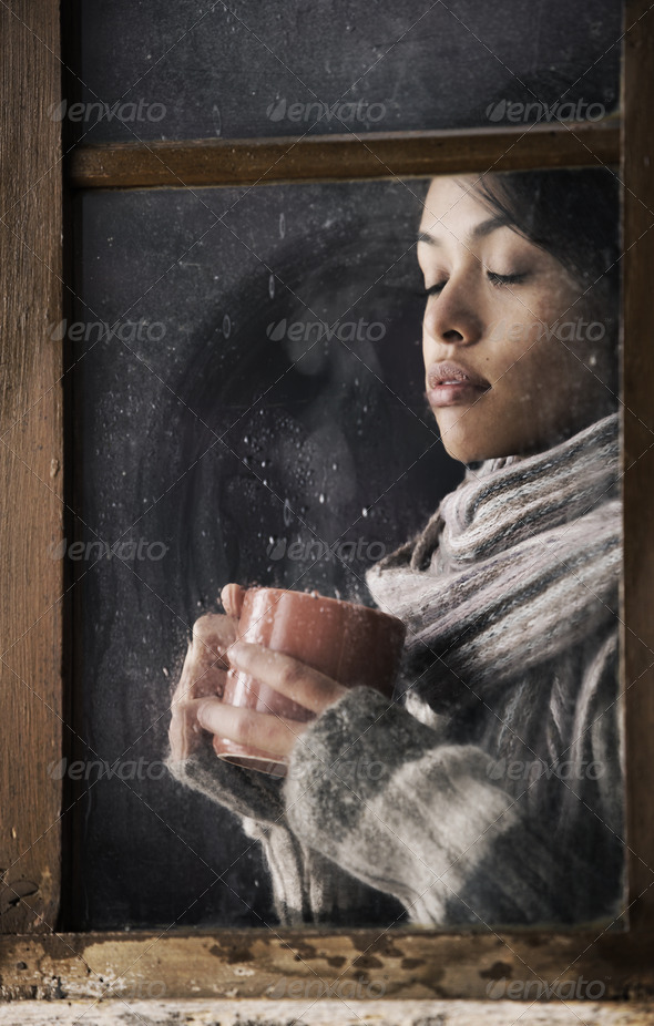 Girl behind window with a cup of coffee or tea - Stock Photo - Images