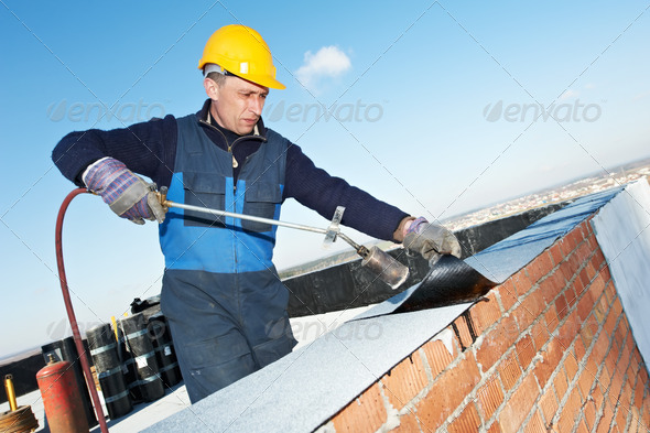 Flat roof covering works with roofing felt - Stock Photo - Images