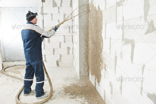 Plasterer at stucco work with liquid plaster - Stock Photo - Images