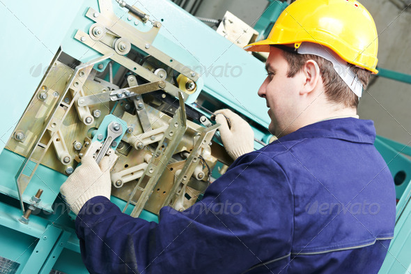 machinist with spanner adjusting lift mechanism - Stock Photo - Images