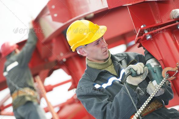 builder worker assembling metal construction - Stock Photo - Images