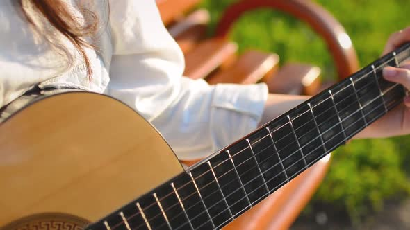 Download Cute Girl Plays on Guitar on the Bench in the Park nulled download