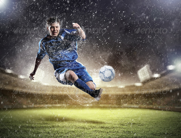 football player striking the ball - Stock Photo - Images