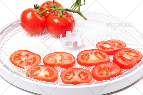 Ripe tomato on food dehydrator tray - Stock Photo - Images