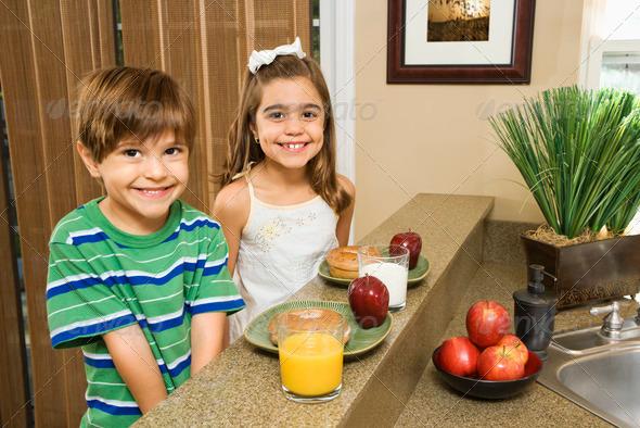 Kids eating breakfast - Stock Photo - Images
