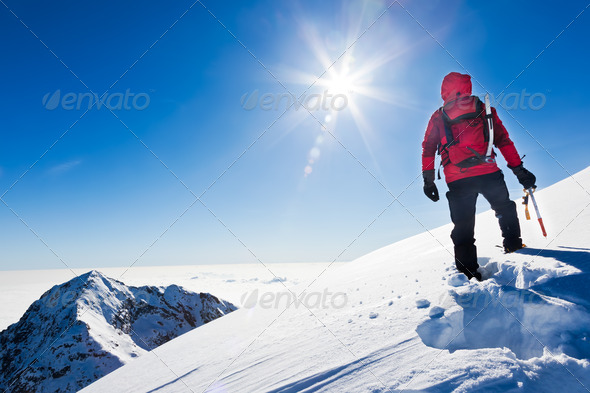 Mountaineer reaches the top of a snowy mountain in a sunny winter day. Western Alps, Biella, Italy. - Stock Photo - Images