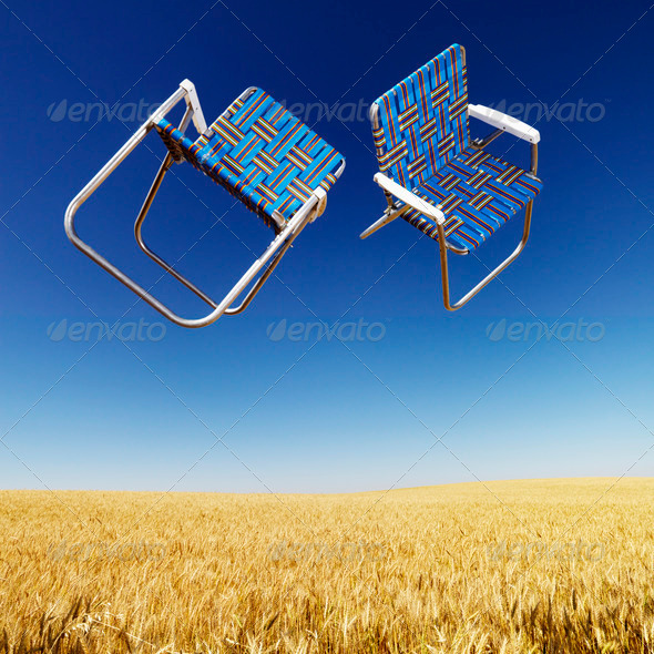 Lawn chairs over wheat field - Stock Photo - Images