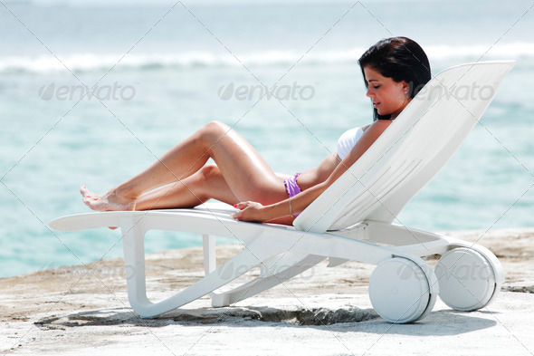 Woman in chaise-lounge near sea - Stock Photo - Images