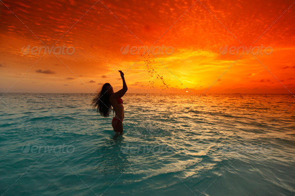 Woman splashing in sea on sunset - Stock Photo - Images