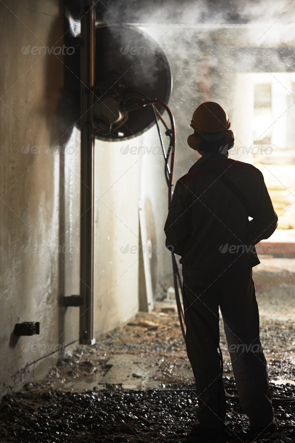 builder worker operating demolition machine - Stock Photo - Images