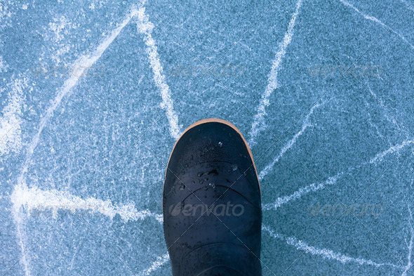 Danger thin ice radially cracks under rubber boot - Stock Photo - Images