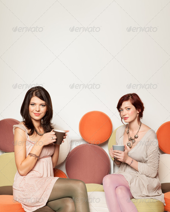 girlfriends on sofa with coffee mugs - Stock Photo - Images