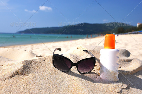 PhotoDune Sunglasses and lotion on the sandy beach of Phuket island Thail 4001884