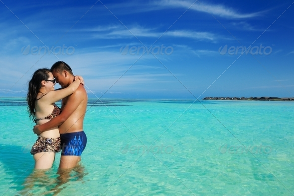 asian couple enjoying summer on beach - Stock Photo - Images