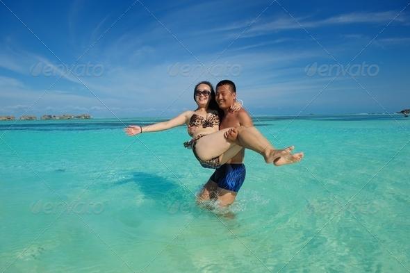 asian couple enjoying summer on beach - Stock Photo - Images
