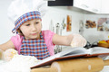 Little girl preparing cookies with cookbook - PhotoDune Item for Sale