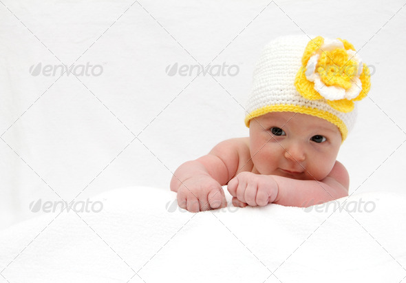 PhotoDune Baby with a knitted white hat baby on stomach 4024085