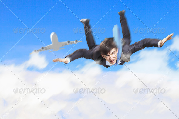 Young businessman flying with parachute on back - Stock Photo - Images