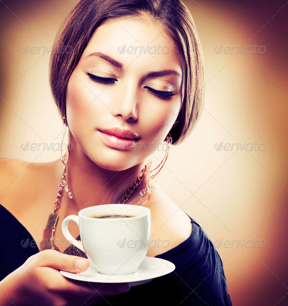 Beautiful Girl Drinking Tea or Coffee. Sepia Toned - Stock Photo - Images