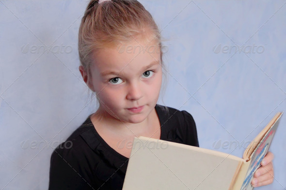 PhotoDune Girl with blond hair reading a book 4082113