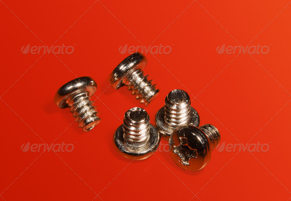 PhotoDune Screws for assembly of a computer on a red table 4082521