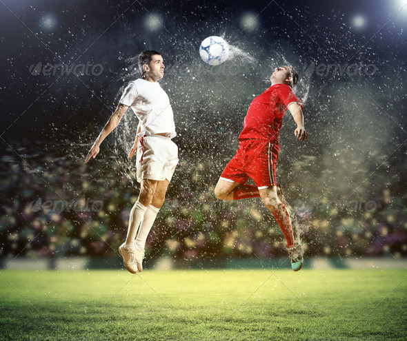 two football players striking the ball - Stock Photo - Images