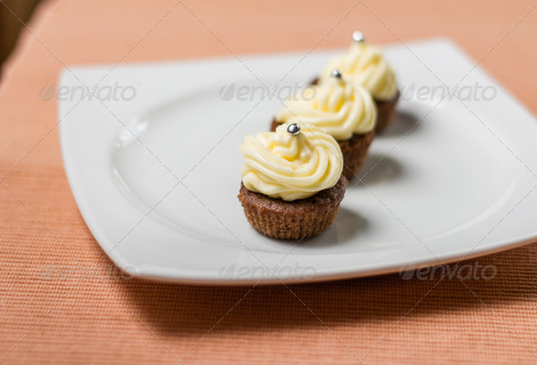 PhotoDune Chocolate cupcakes with silver sprinkles on top on white plate 4112111