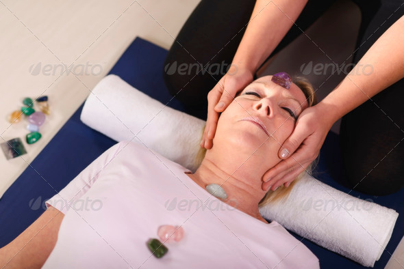 Young therapist arranging crystals on female client for reiki th - Stock Photo - Images