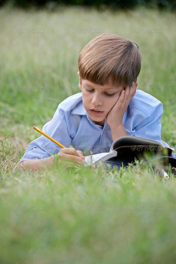Young school boy doing homework alone, lying on grass - Stock Photo - Images