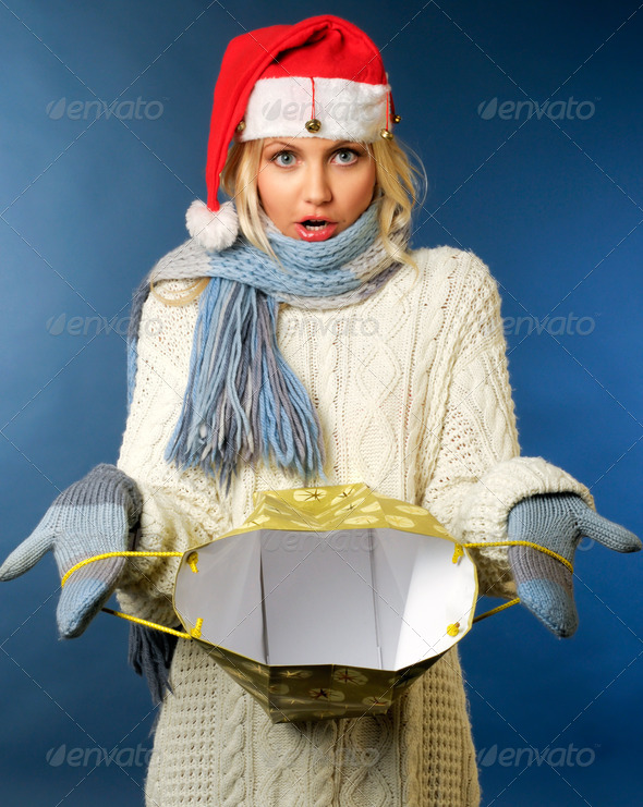 blonde girl in santa hat with gift bag - Stock Photo - Images