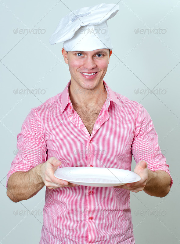 Young handsome chef holding empty plate - Stock Photo - Images