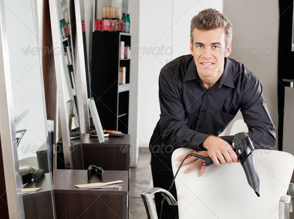 Male Hairstylist With Hairdryer Leaning On Chair - Stock Photo - Images