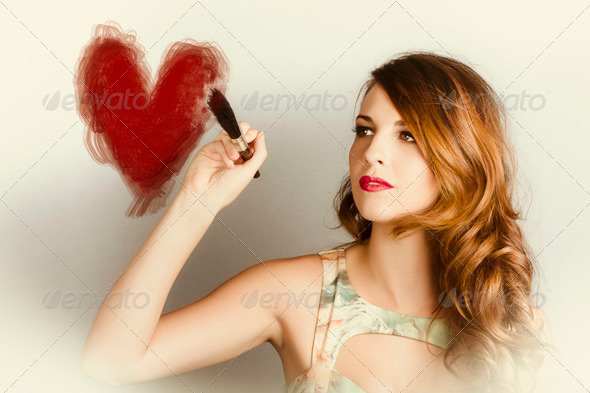 Beautiful retro girl painting red love heart - Stock Photo - Images
