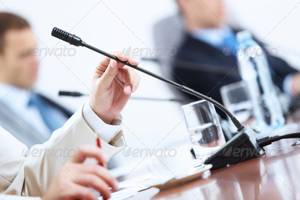 Hands of businessman holding microphone - Stock Photo - Images