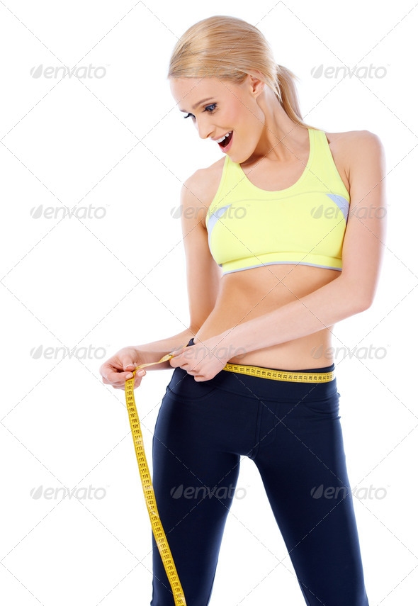 Surprised blond sporty woman measuring her waist - Stock Photo - Images