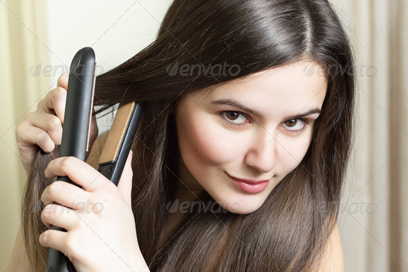 Beautiful young woman ironing her hair - Stock Photo - Images