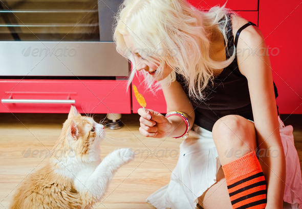 Beautiful blonde girl with candy in hand and cat sitting on kitchen floor
