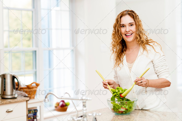 Smiling woman tossing salad in kitchen - Stock Photo - Images