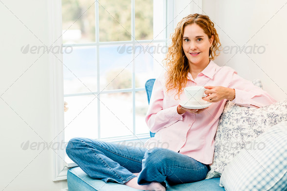 Woman relaxing by the window with beverage - Stock Photo - Images