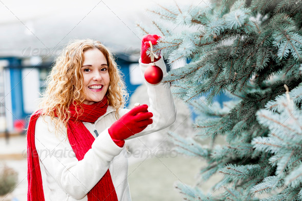 Woman decorating Christmas tree outside - Stock Photo - Images