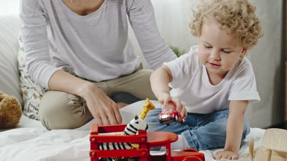 Download Angelic Little Boy Playing with Wooden Toy Cars nulled download