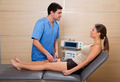 Doctor therapist checking muscle electrostimulation to woman - PhotoDune Item for Sale