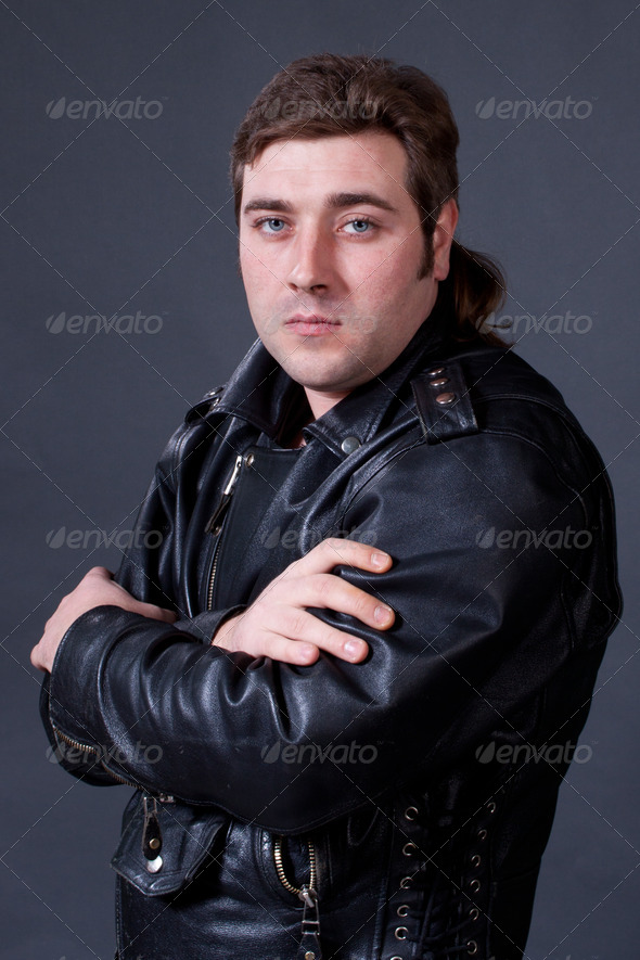 PhotoDune young man in a leather jacket on a gray background shot in studi 4307247