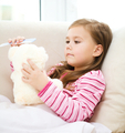 Little girl is combing her teddy bear - PhotoDune Item for Sale