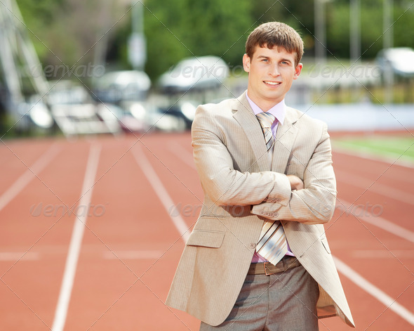 Businessman at athletic stadium and race track - Stock Photo - Images
