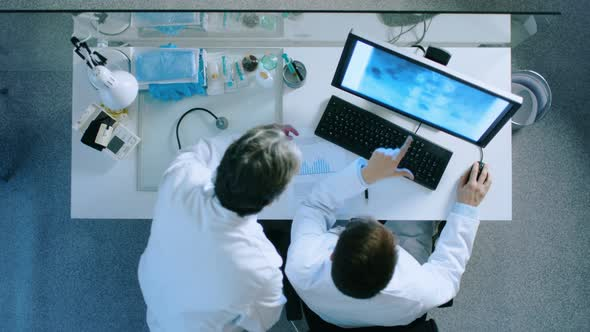 VideoHive Two Doctors at the Working Desk Discussing Patient's X-Ray Shown on a Monitor Screen 19478711