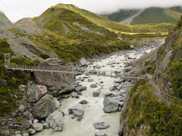 Swing bridge over mountain river in New Zealand - Stock Photo - Images