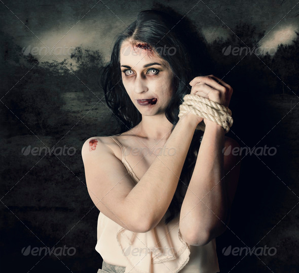 Dark horror scene of an evil zombie woman tied up - Stock Photo - Images